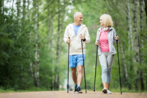 A senior man and woman walking in the woods to ease joint pain