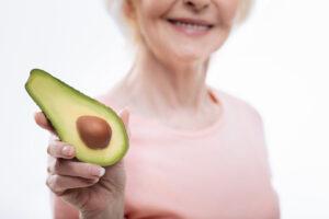 Senior woman holding half an avocado. Foods to help arthritis