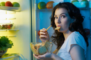 Woman eating from fridge. Foods to avoid